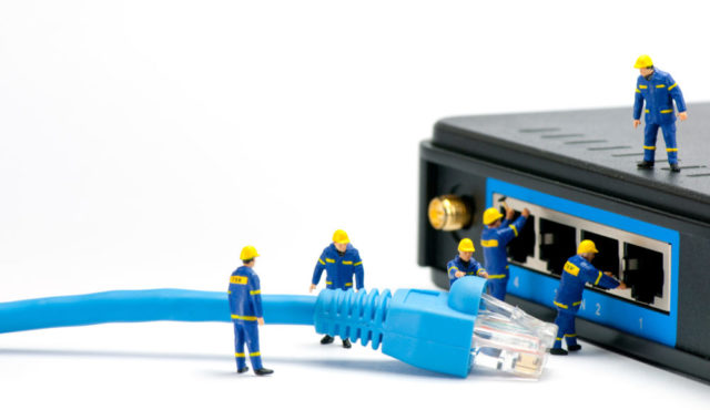 Toy technicians connecting a network cable to the back of a device.