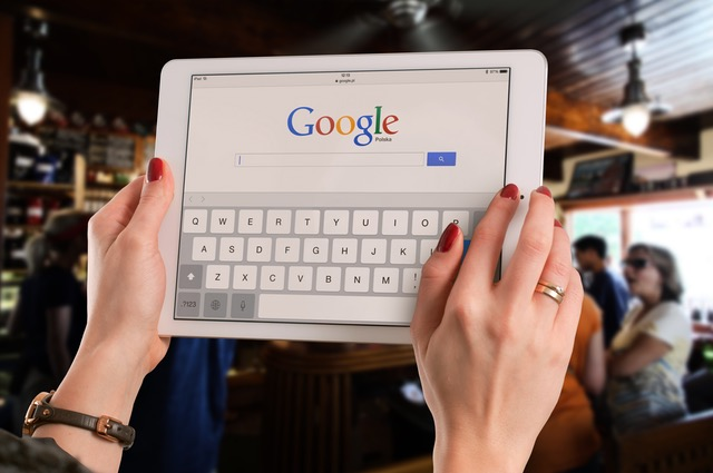 Picture of a woman holding a tablet with Google browser on the screen.